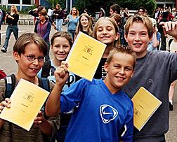 Schüler mit Zeugnis-Hefte in der Hand