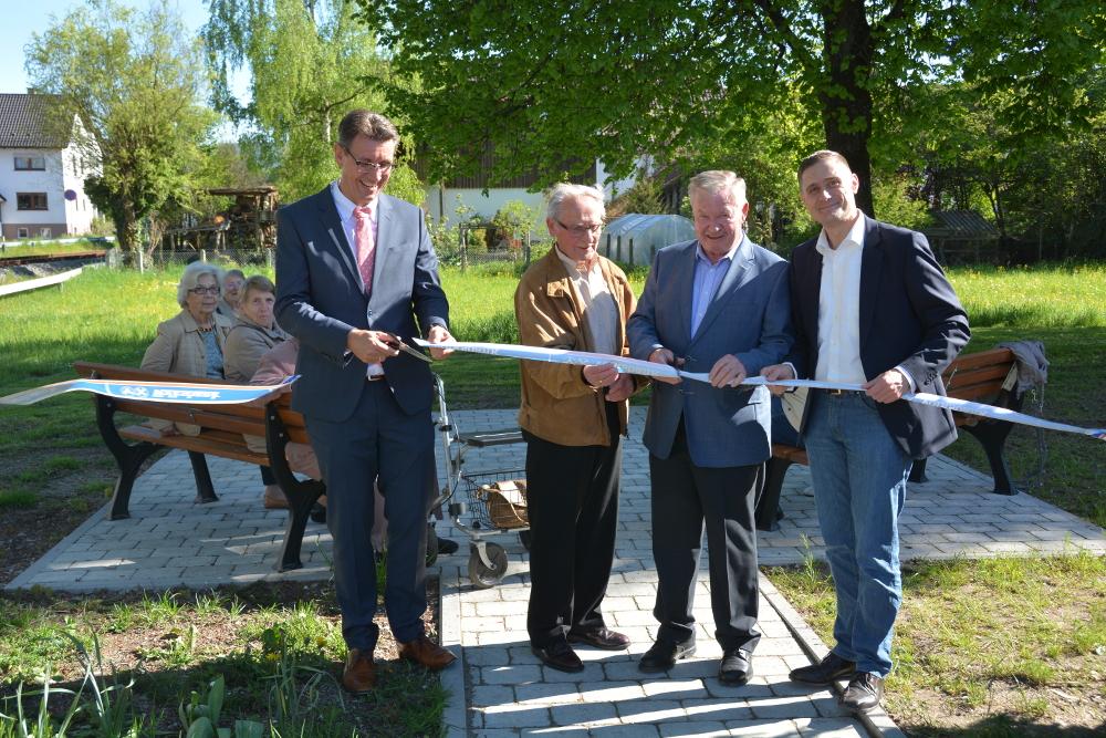 Bürgermeister Thorsten Englert, Karl Rak, Ortsvorsteher Erich Bühler und Steffen Schultheiß, Fachbereichsleiter Gebäudemanagement (v.l.), eröffnen den Seniorensitzplatz.