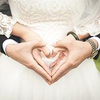 Ein Hochzeitspaar bildet ein Herz mit den Händen