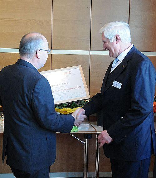 Herbert Titze überreicht Urkunde zum Kreisehrenhandwerksmeister an Roldnad Wöhr