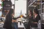 Vier Frauen stoßen in einer Bar mit einem Glas Wein an