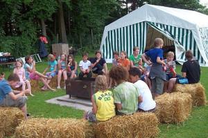 Einige Kinder sitzen bei der Stadtranderholung auf Heuballen, im Hintergrund ist ein Zelt