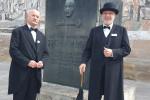 Zwei Stadtführer, als Gottlieb Daimler verkleidet, stehen vor dem Gottlieb Daimler Denkmal.