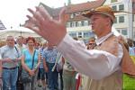 Ein Stadtführer, verkleidet als der Arme Konrad, steht bei einer Stadtführung vor einer Gruppe von Menschen und hebt seine Hand.