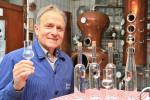 Hans Böhringer hält in der Familien-Brennerei ein Schnapsglas in seiner Hand, im Hintergrund sind Schnapsbrenner zu sehen.