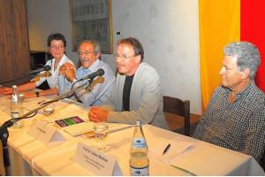 Vier Personen sitzen an einem Tisch, einer hat ein Mikrofon