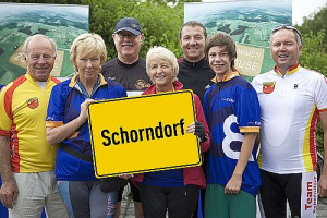 Das Team aus Schorndorf steht zusammen und zwei Frauen halten das Schorndorfer Ortschild in ihren Händen