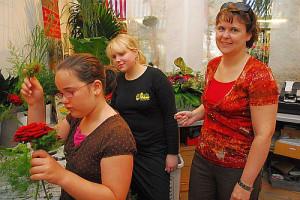 Zwei Frauen und ein Kind binden gemeinsam einen Blumenstrauß