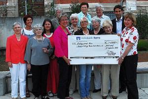 Mehrere Personen nehmen einen Spendenscheck an die Hospizstiftung an