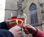 Drei Personen stoßen mit einem Glas Wein an