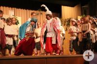 Eine Gruppe führt ein Theaterstück auf einer Bühne auf