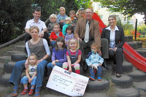 Einige Kinder und Erwachsene sitzen auf einem Spielplatz und halten einen Scheck in ihren Händen