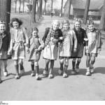 Sieben Mädchen mit Holzschuhen und Schürzen auf dem Weg zur Schule, 1948