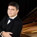 Pavlos Hatzopoulos steht vor einem Klavier