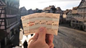 Eine Hand hält Schorndorf Tickets. Im Hintergrund der Marktplatz.