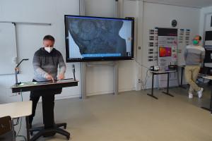 Geografie- und Mathelehrer Steffen Sieber (links) vergrößert über der Pilotstation die Ansicht einer Versteinerung.