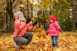 Frau und Kind spielen im Laub