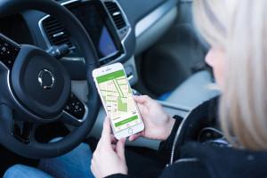 Eine Frau sitzt im Auto und hat auf ihrem Handy die Parkster App geöffnet