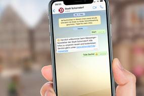 Eine Hand hält ein Smartphone, auf dem WhatsApp geöffnet ist.