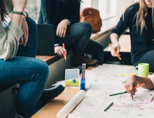 Vier Personen sitzen um einen Tisch herum und schreiben etwas auf ein Blatt Papier