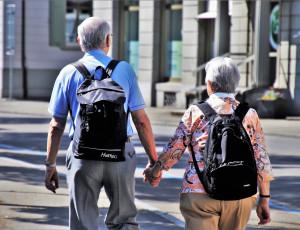 Seniorenpaar läuft mit Rucksack auf einer Straße