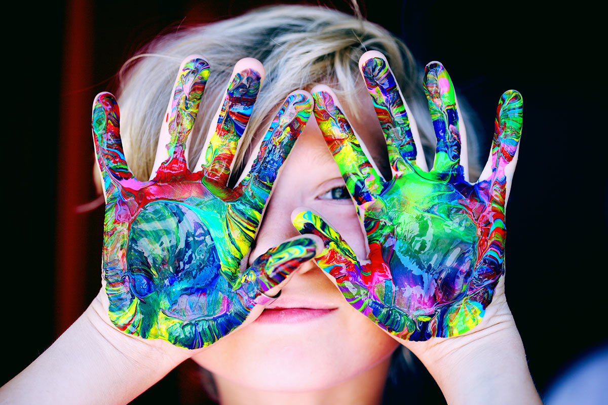 Kind mit Wasserfarbe an den Händen