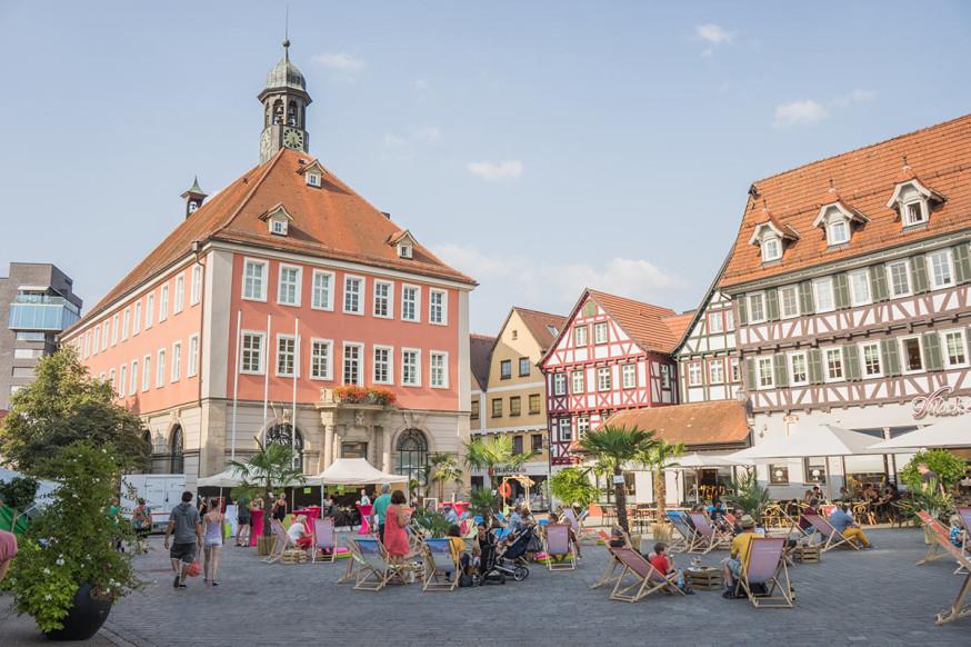 Blick auf den Schorndorfer Marktplatz, mit Liegestühlen, Palmen und Besuchern und dem Rathaus im Hintergrund