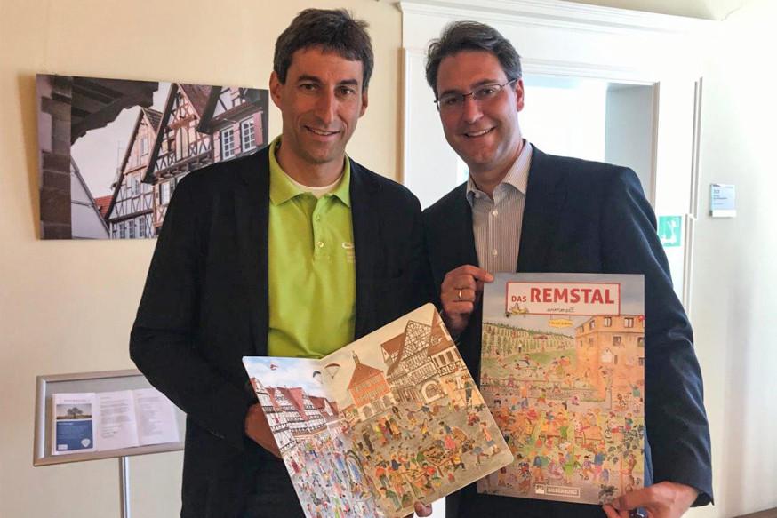 Landrat Dr. Richard Sigel (r.) überreichte OB Matthias Klopfer das neue Wimmelbuch.