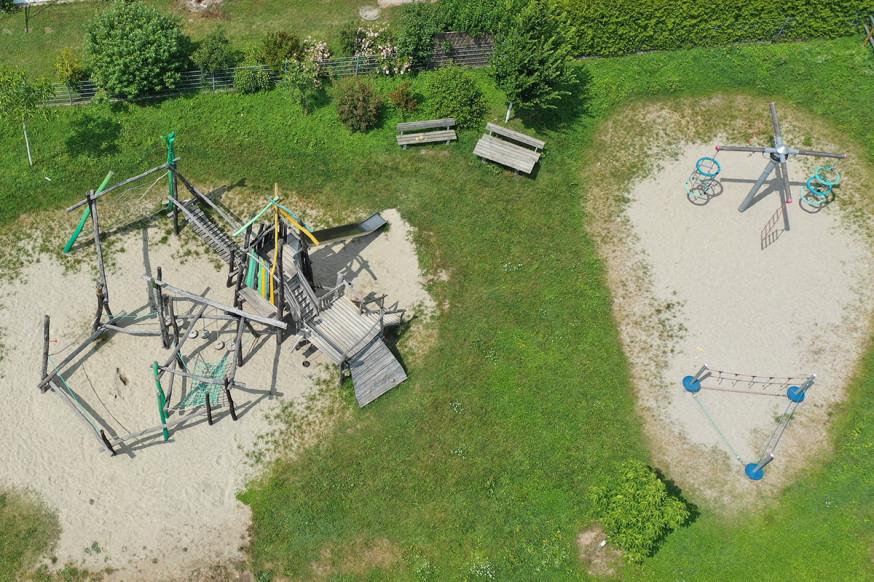 Ein weitläufiger Spielplatz mit abwechslungsreichen Spielgeräten und Sitzgelegenheiten.