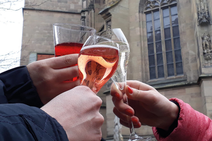 Drei Gläser mit unterschiedlichem Wein werden zusammengehalten, im Hintergrund die historische Stadtkirche.