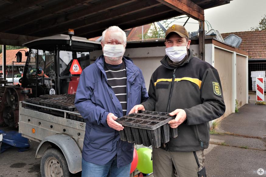 Julian Schmitt (rechts) überreicht Dieter Wietreck einen Pflanzcontainer.