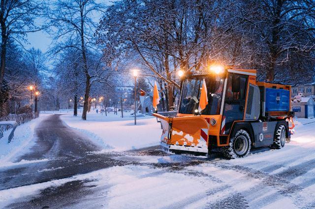 Räum-und Streufahrzeug befreit die Fußwege im Schlosspark von Schnee