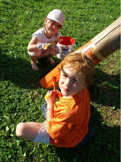 Kinder bemalen die Schaukel auf dem Spielplatz Pappelweg