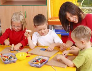 Erzieherin spielt mit den Kindern an einem Tisch